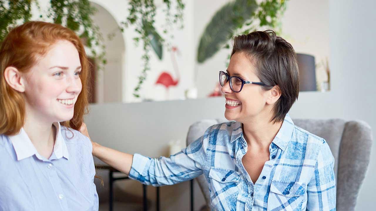 Eine Frau macht einer anderen ein Kompliment, beide freuen sich
