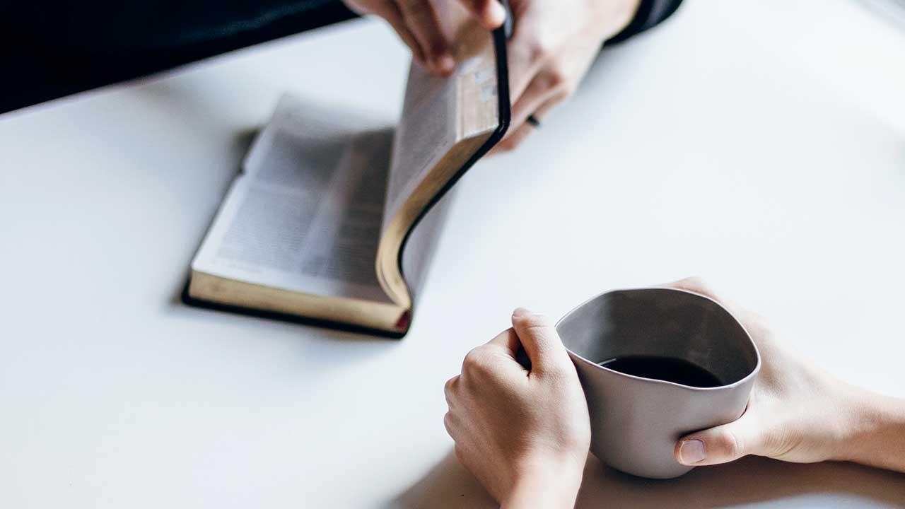 Ein paar Hände hält eine offene Bibel, ein anderes paar Hände hält eine Tasser