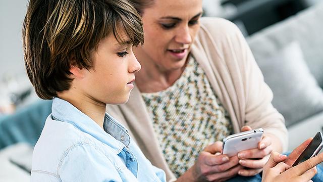 Sohn und Mutter mit Smartphones