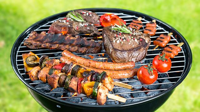 Fleischstücke und Tomaten auf dem Grill